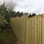 Featherboard fence panels on slotted fence posts